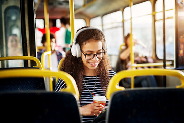 A gorgeous cheerful young woman with curly hair is sitting in the bus seat listening to music drinking coffee and using a tablet.