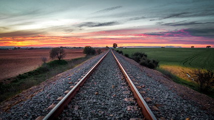 Printed roller blinds Railroad train tracks in the middle of the field with red sunset background
