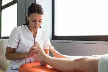 Young woman in medical uniform massaging feet of crop patient during physiotherapy session.
