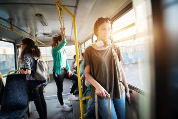 Young charming woman with headset around her neck traveling by bus and holding her luggage while leaning against the bus bars.