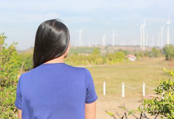 Rear view of Asian woman against wind turbine field.
