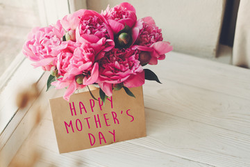 happy mother's day text on craft card and pink peonies bouquet on rustic white wooden window in light. floral greeting card concept. mothers day. soft tender spring image