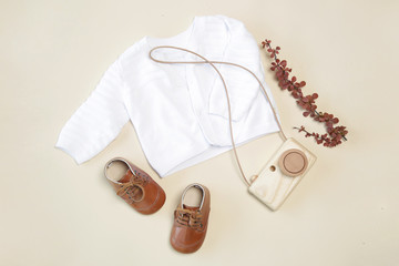 Baby outfit, top view, white sweather, shoes and wooden camera toy