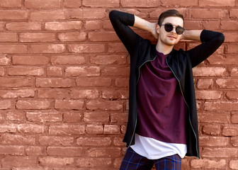fashion guy in glasses stands near a brick wall with cracked paint