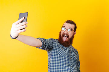 Funny bearded man wearing eye glasses and taking selfie over yellow background