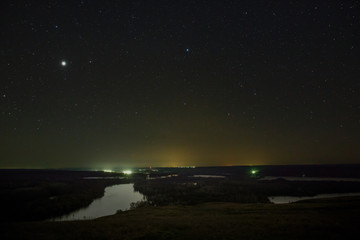 Planet Jupiter and stars in the night sky. A view of the starry space in the background of a landscape with a river.