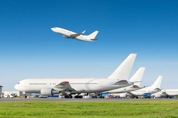 Passenger aircraft row, airplane parked on service before departure at the airport, other plane push back tow. One take off from the runway in the blue sky. Wall mural