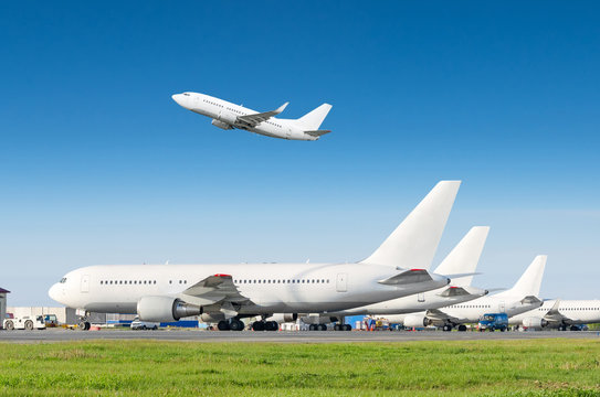 Passenger aircraft row, airplane parked on service before departure at the airport, other plane push back tow. One take off from the runway in the blue sky.