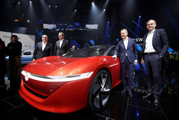Herbert Diess, Volkswagen's new CEO, and another company leader pose for a photo next to a Volkswagen I.D. concept car at a media event in Beijing