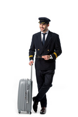 smiling pilot in uniform with luggage isolated on white
