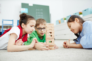 Multiethnic group of elementary school children lying on the floor and playing with wooden blocks after classes