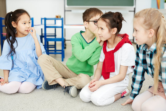 Primary school kids whispering words to each other while playing telephone game in classroom after lessons