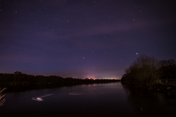 The lake in the Park at night. Starry sky above the trees. The city lights at night.