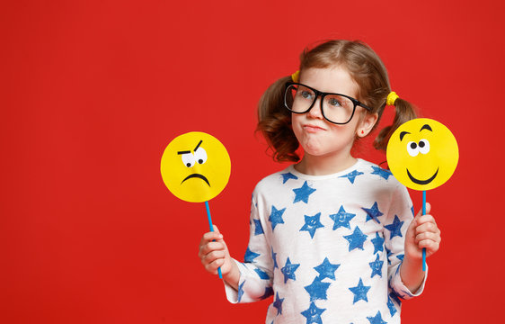 concept of children's emotions. child girl chooses between a sad and joyful smile