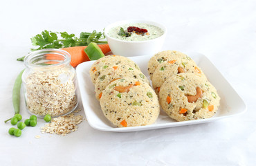 Oats Idli or cake, a healthy Indian vegetarian food, with vegetables like carrot, peas, green beans and capsicum, and cashew nuts, which is steam cooked.