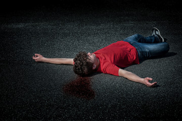 Crime scene - dead teen boy body in blood on asphalt(staged photo). Body of a young childlying on the street road.