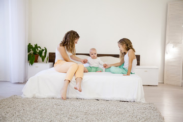 three girls play sisters in the morning in the bedroom on the bed