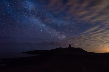 Milky Way above Dunstanburgh Castle / Dunstanburgh Castle at night on the Northumberland coastline in England