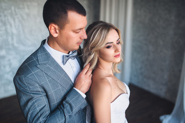 Beautiful and modern newlyweds stand in a gray studio. A stylish groom adjusts the hair to a sweet bride with curly hair. Portrait of a newlywed couple.
