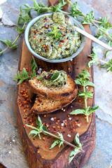 Schüssel mit Oregano Pesto und getoasteten Brot auf einem Olivenholz-Brett