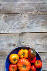 rustic organic tomatoes for vegetarian menu over vintage wooden background