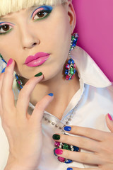 Fashionable colorful short nail art design on female hand close up with decoration on the face.Blue green pink nail Polish.On-trend manicure.