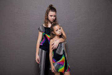 fashion portrait of two girls on a grey background