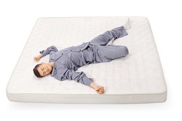 Teenage boy sleeping on a mattress