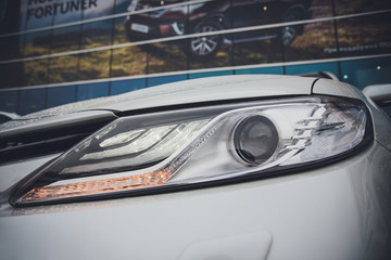 front headlight with brilliant reflections auto white body car detail