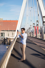 Man taking picture on Erasmus bridge