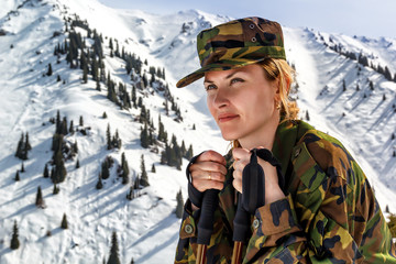 young woman in khaki uniform with walking sticks on a background of snow-capped mountains