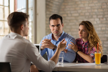 Young couple meeting with their financial advisor.