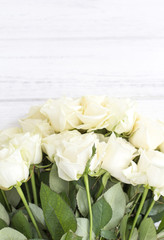 White roses on a white wooden background. Bouquet of white roses