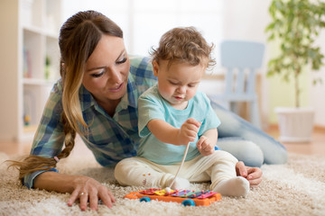 Baby toddler boy and mom playing in white sunny bedroom. Kids with educational toy in nursery.