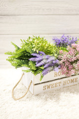 Flowers in a white wooden box. Interior decoration, interior composition. Flowers and branches in a wooden box on a white wooden background