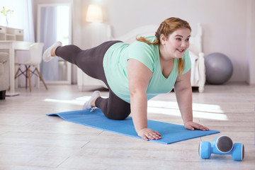 Basic exercises. Red-head young woman standing on the yoga mat while doing exercise