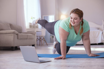 Video lesson. Obese young woman repeating exercises while watching online workout session