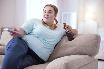 Alcohol disaster. Lazy obese woman drinking beer while sitting on the sofa
