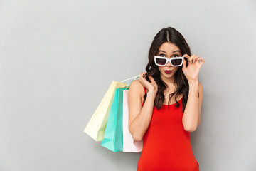 Surprised brunette woman in casual clothes and sunglasses with packages