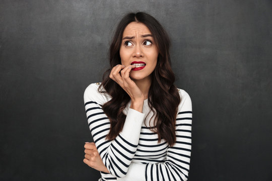 Worried pensive brunette woman in sweater bites her nails
