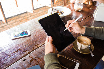 Man hand use tablet blank screen on wood table with hot latte