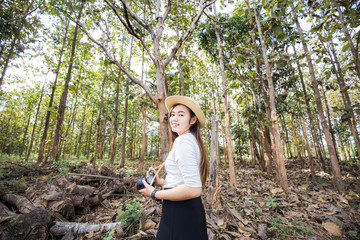 Photographer asian women travel in forest with camera