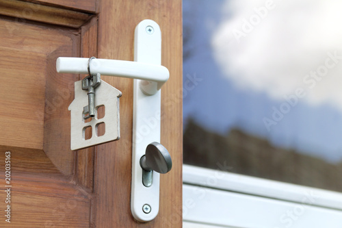 Residential Real Estate/ key and house symbol hangs on the handle of the front door & Residential Real Estate/ key and house symbol hangs on the handle of ...