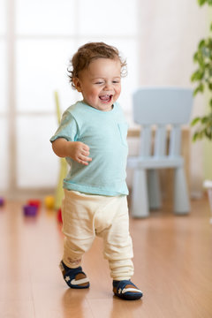 First steps of baby boy toddler learning to walk in living room. Footwear for little children.