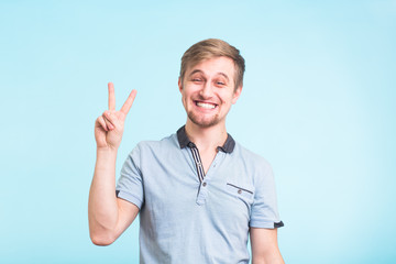 Cheerful young man in polo t-shirt showing victory sign and smiling at camera isolated on blue background