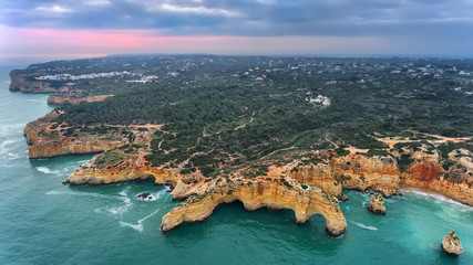 Aerial. Mountains and arches in the shape of a heart on the beach Marinha.