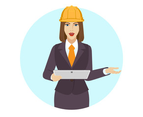 Businesswoman in construction helmet  holding a digital tablet PC and howing something beside of her