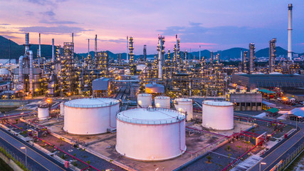 Aerial view oil and gas chemical tank with oil refinery plant background at twilight, business power and energy chemical barrel.