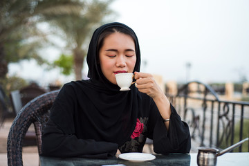 Muslim woman having a cup of coffee outdoors