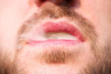 Man's lips and cigarette smoke close up